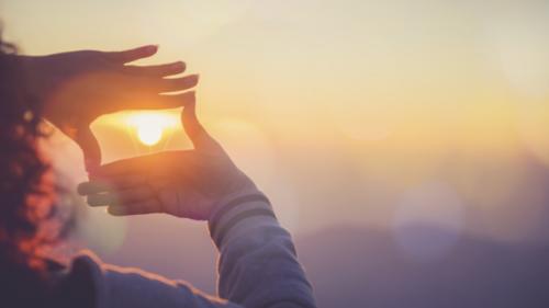 Hände bilden Rahmen um Sonne im Sonnenuntergang